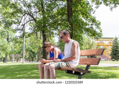 horizontal image of a father and son sitting on a park bench texting on their cell phones on  warm summer afternoon.
