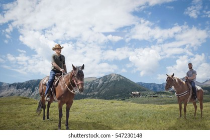 horizontal image of a father and teenage son out horse back riding as they sit on their horse and pose for camera with mountains and blue sky over head in the summer time.