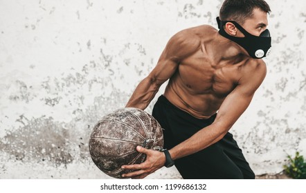 Horizontal image of fitness muscular male doing exercises with medicine ball in mask on concrete background outdoor. Copy space for advertising. Shirtless sportsman doing workout