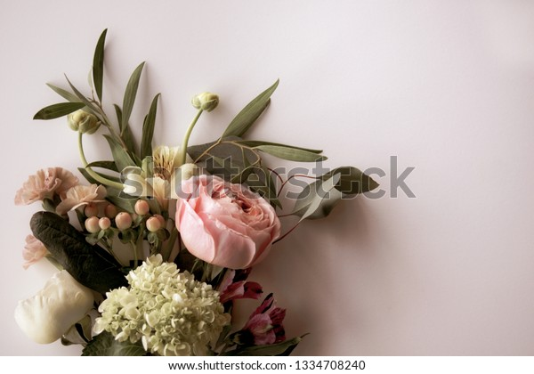 Horizontal image of fresh cut, pink and white flowers, buds, and berries with greenery on a pale pink background with copy space