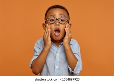 Horizontal image of funny surprised adorable black little boy in round glasses and shirt having astonished shocked facial expression, opening mouth widely and holding hands on his cheeks, shouting