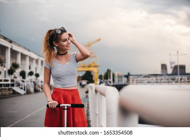 Horizontal image of a girl on a kick scooter leaning against a fence by the river. She is wearing red skirt and T-shirt with stripes