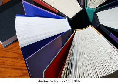 Horizontal image of a group of colorful books standing upright in a circle against a wooden desk.  One book is lying on its side in the background.