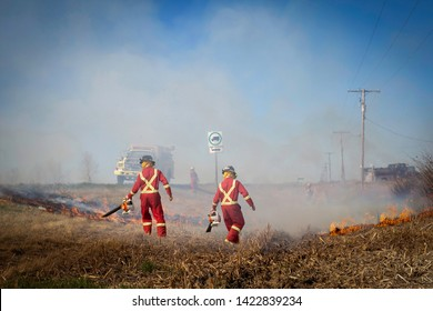 horizontal image of a group of firemen fighting a fire burning in a ditch beside the highway  with smoke filling the air with the firetruck sitting by on a summer day.