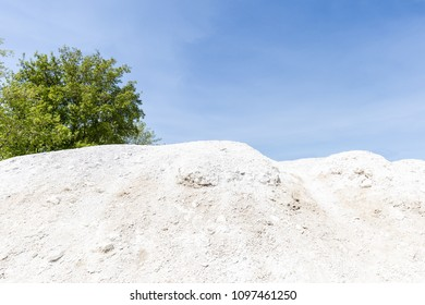 horizontal image of a large pile of white rocks and stones under a blue sky and green trees in the background with room for copy space.