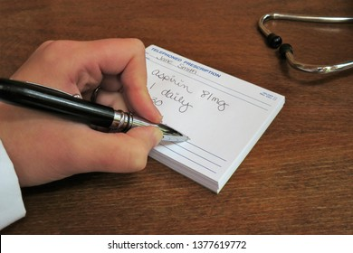 Horizontal image of a left handed doctor (physician)  using a black and silver pen to write a prescription for aspirin with a stethoscope in the background.