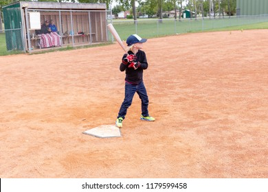 horizontal image of a little caucasian girl standing by the home plate at a baseball game  holding her bat standing ready to swing at the ball in the summer time.