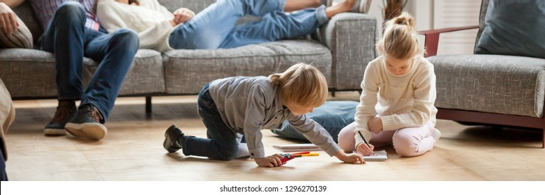 Horizontal image little kids play drawing on warm floor parents resting on couch family spend free time together, leisure activity at modern comfortable home concept, banner for website header design