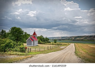 horizontal image of a little rural country church with a red roof surrounded by trees  with gravel road running beside it in the summer time.