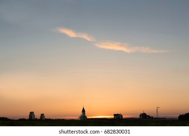 horizontal image of a little semi ghost town with a beautiful big sunset behind it.