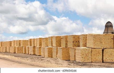 horizontal image of a lot of lumber stacked and piled at the saw mill under a bright cloudy sky in the summer time.