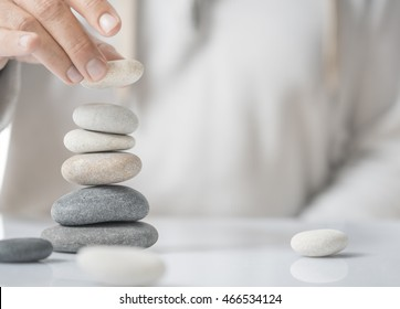 Horizontal image of a man stacking pebbles on a table with copyspace for text. Concept of personal development or self realization.