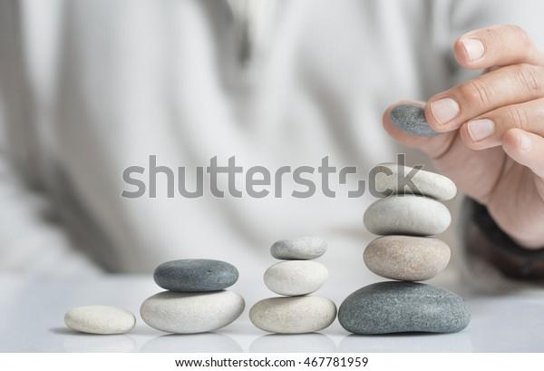 Horizontales Bild eines Mannes, der Kieselsteine stapelt, auf einem Tisch mit Kopienraum für Text. Konzept von Risikomanagement und Wohlstand.