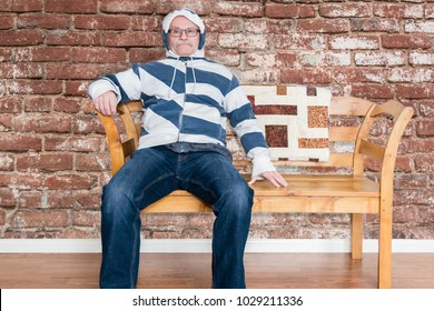 horizontal image of a middle aged caucasian man sitting on a wooden bench in a foul mood inside his home.