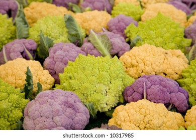Horizontal image of a mix of Romanesco broccoli, purple and orange cauliflower.