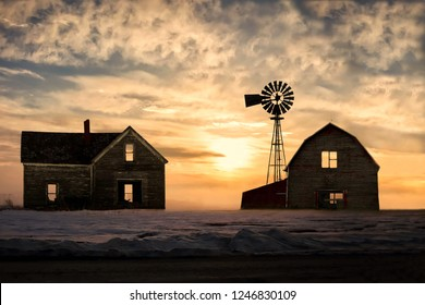 horizontal image of a an old abandoned farm house and barn looking desolate with a beautiful ornage sunset looming in the background on a cold winter evening..