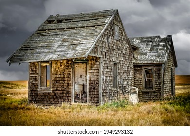horizontal image of an old abandoned small house with cedar shingle siding with broken windows and a wringer washing machine sitting outside under a dark cloudy sky in the fall.
