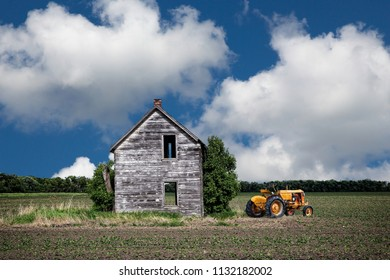 horizontal image of an old antique tractor sitting in a field next to an old  gray wooden  shed under a blue sky with white clouds floating by in the summer time