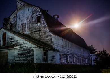 horizontal image old barn with full moon coming up behind.  Night shot using light painting to show abandoned barn and purple night sky with star burst effect on moon.
