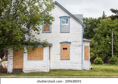 "horizontal image of an old condemned house with windows boarded up and ""no trespassing sign"" with big tree in front in summer time"