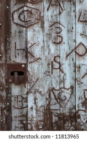 Horizontal image of an old door covered in western branding iron marks