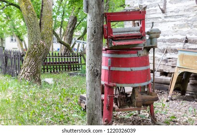 horizontal image of an old wooden antique red wringer washing machine sitting outside.