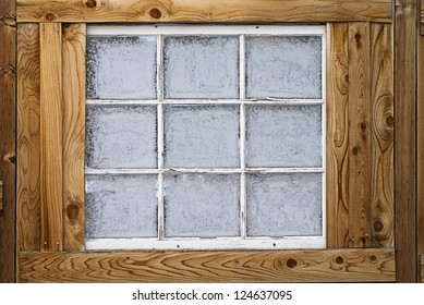 Horizontal image of an old wooden nine-lite window pane in a wooden wall, covered in ice crystals.