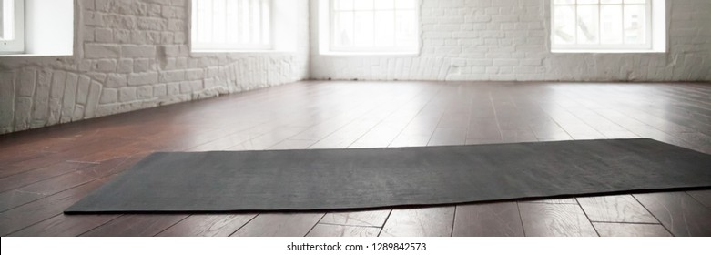 Horizontal image personal yoga pilates rubber mat carpet on wooden floor at modern room of sport center no people. Healthy active lifestyle concept, panoramic photo banner for website header design