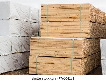 horizontal image of a pile of lumber stacked and tied together.