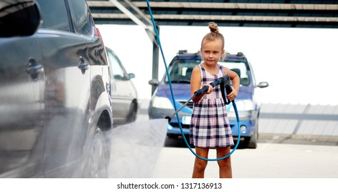 Horizontal image pretty adorable little preschool girl in summer dress helping to parents use coin-operated self-serve car wash, clean auto exterior holding high-pressure sprayer standing outdoors
