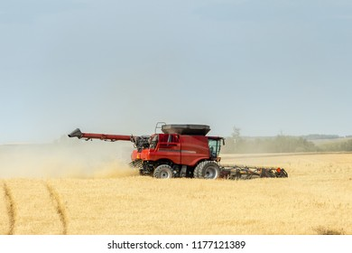 horizontal image of a red combine in the golden wheat field combining the  crop in the fall time .