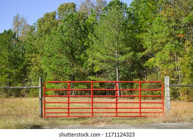 horizontal image of a red entry gate to a field in the country