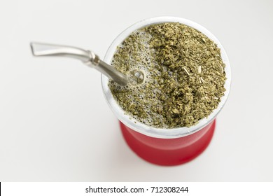 Horizontal image of a red mate with a delicious steaming yerba mate infusion, a traditional South American, caffeine-infused drink.