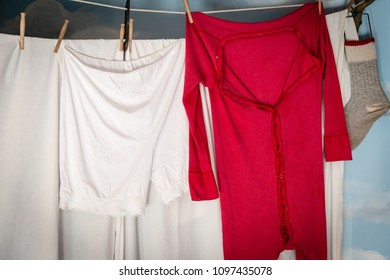 horizontal image of a red pair of long johns hanging from a clothes line with copy space.
