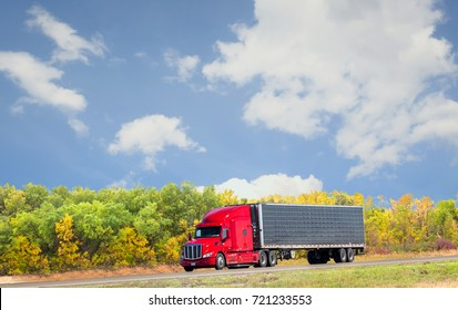 horizontal image of a semi truck with a red cab driving down the highway with beautiful fall coloured trees under a nice blue sky with white clouds on a warm fall sunny day with copy space.