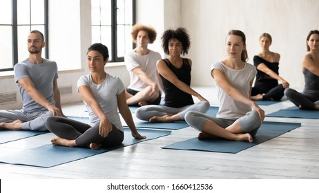 Horizontal image seven multi-ethnic people during yoga class seated in lotus position performing Easy Twist Pose or Parivrtta Sukhasana. Exercise decrease feeling of nervousness, reduce stress concept