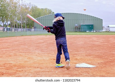 horizontal image of a small caucasian 5 year old girl batting the base ball into the air on a cloudy summer day.