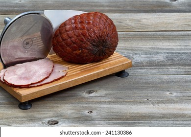 Horizontal image of smoked ham and meat slicer machine on rustic wood