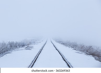 horizontal image of snow covered train tracks leading into a thick fog, with copy space / Train Tracks leading into the Fog