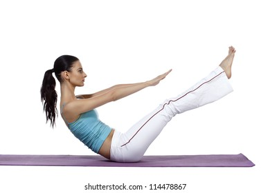 Horizontal image of a sporty woman stretching her legs and arms while lying on the mat