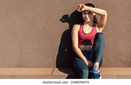 Horizontal image of a sporty young woman resting after training outdoors on a sunny day.  Athelete smiling girl relaxing after stretching in the morning sunlight outside.