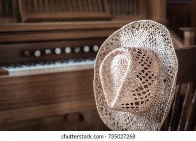 4601452aca5 horizontal image of a straw cowboy hat hanging on a chair next to the  church organ