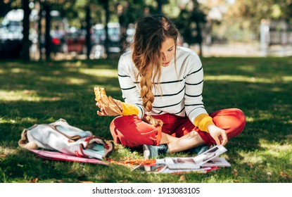 Horizontal image of a student female sitting on the green grass at the college campus on a sunny day, have lunch and studying. The hungry young woman takes a rest learning and eating in the park.
