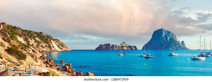 Horizontal image summer at Cala d'Hort sandy beach, in summer is extremely popular, beach have fantastic view of mysterious island of Es Vedra. Ibiza Island, Balearic Islands. Spain