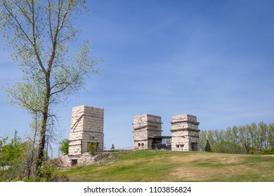 horizontal image of three tall old abandoned brick limestone kilns sitting on a hill in the summer time under blue skies with lots of copy space.