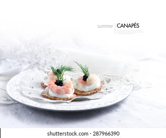 Horizontal image of Tiger prawn, caviar and cream cheese canapes in a vintage setting against a white, bright background. A perfect image for your wedding breakfast cover design. Generous copy space.