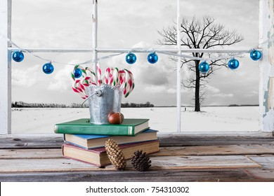 horizontal image of a tin pail sitting on top of books filled with Christmas candy canes in front of window with blue balls strung across the frame with a winter scene on the outside.