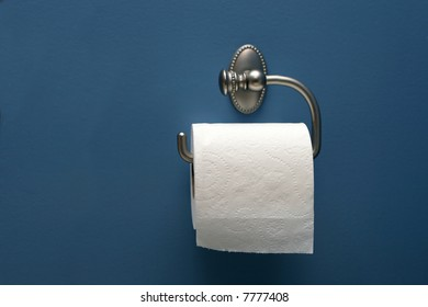 horizontal image of toilet paper on blue wall, straight on