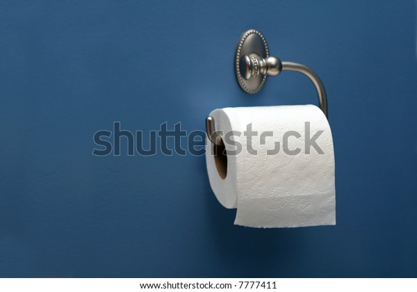 horizontal image of toilet paper on blue wall, right.