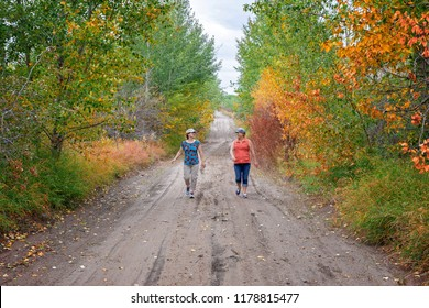 horizontal image of two caucasian ladies walking  down a rural country road in the fall time talking and laughing.